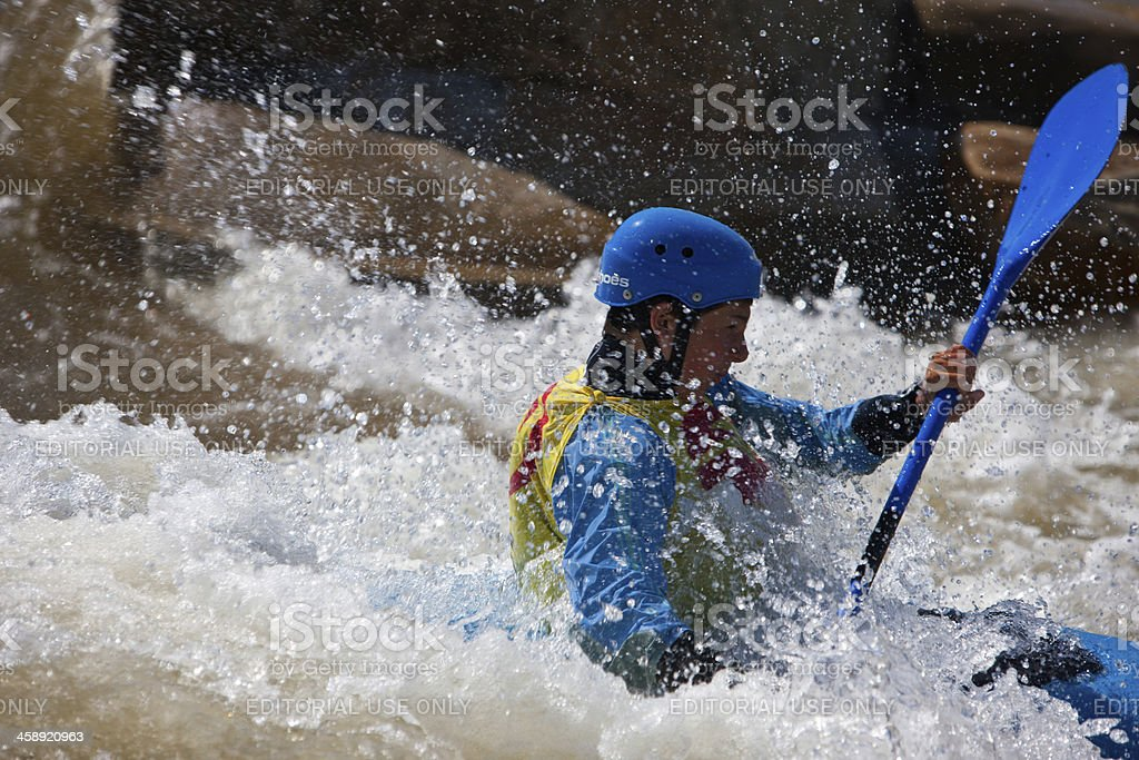 Kayaker Splashes Through A Wave and Spray stock photo
