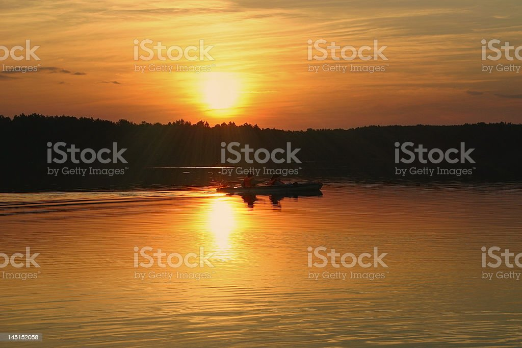 kayakers against summer sunset stock photo