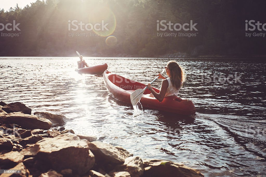 kayakers rowing on a lake stock photo