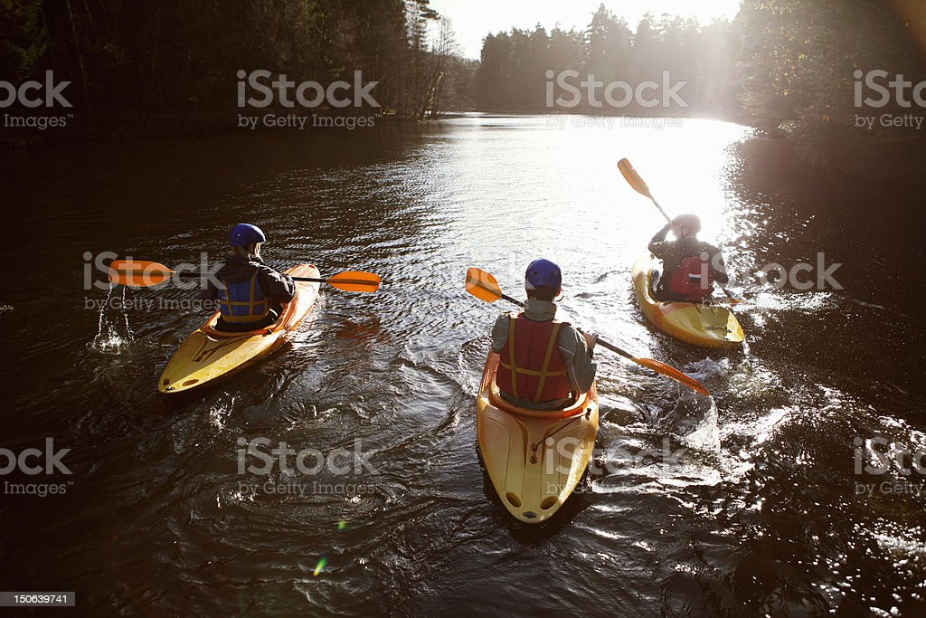 Kayakers rowing together on still lake stock photo