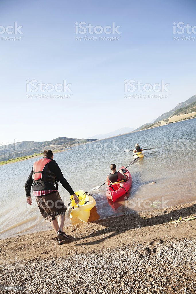 Kayakers taking their kayaks out on a lake royalty-free stock photo