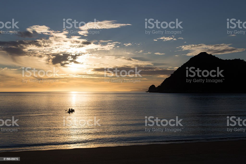 Kayaking at sunrise in Abel Tasman National Park stock photo