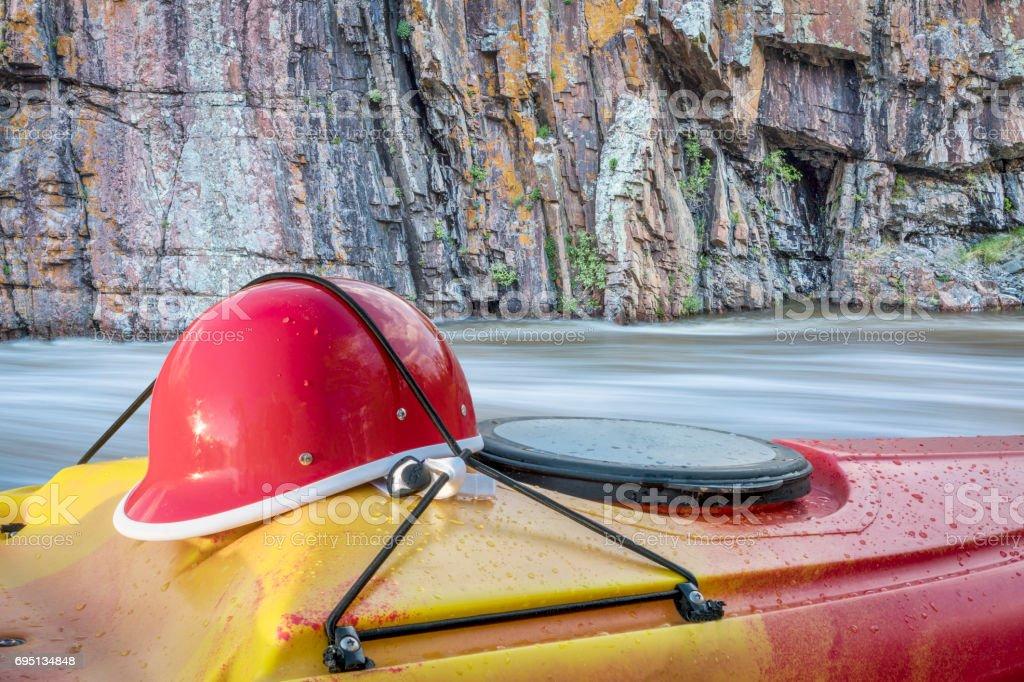 kayaking helmet on kayak deck stock photo