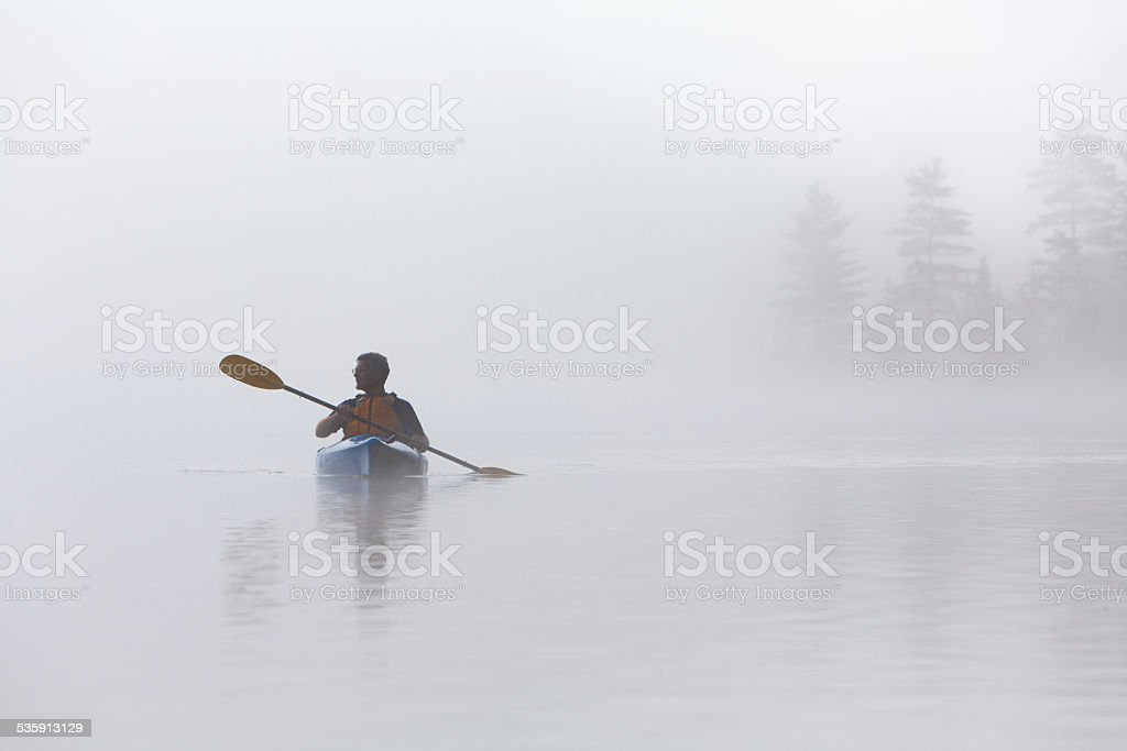 Kayaking in Early Morning Fog stock photo