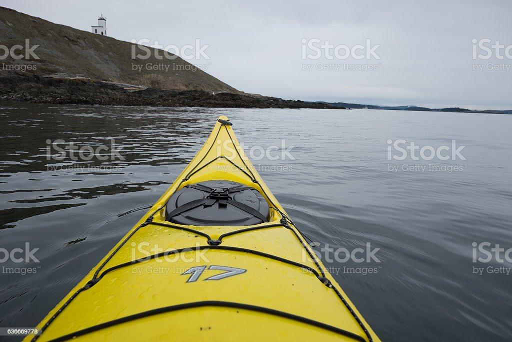 Kayaking past lighthouse on San Juan Island stock photo