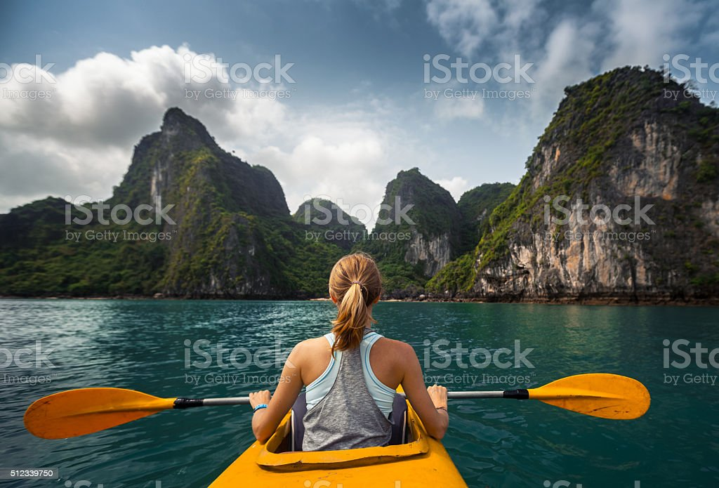 Woman exploring calm tropical bay with limestone mountains by kayak....