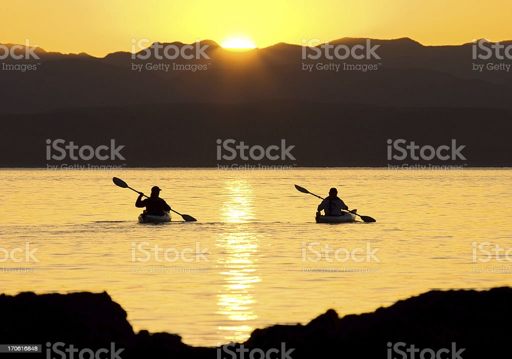 Kayaking sporty outdoor couple sea-canoeing at sunset stock photo