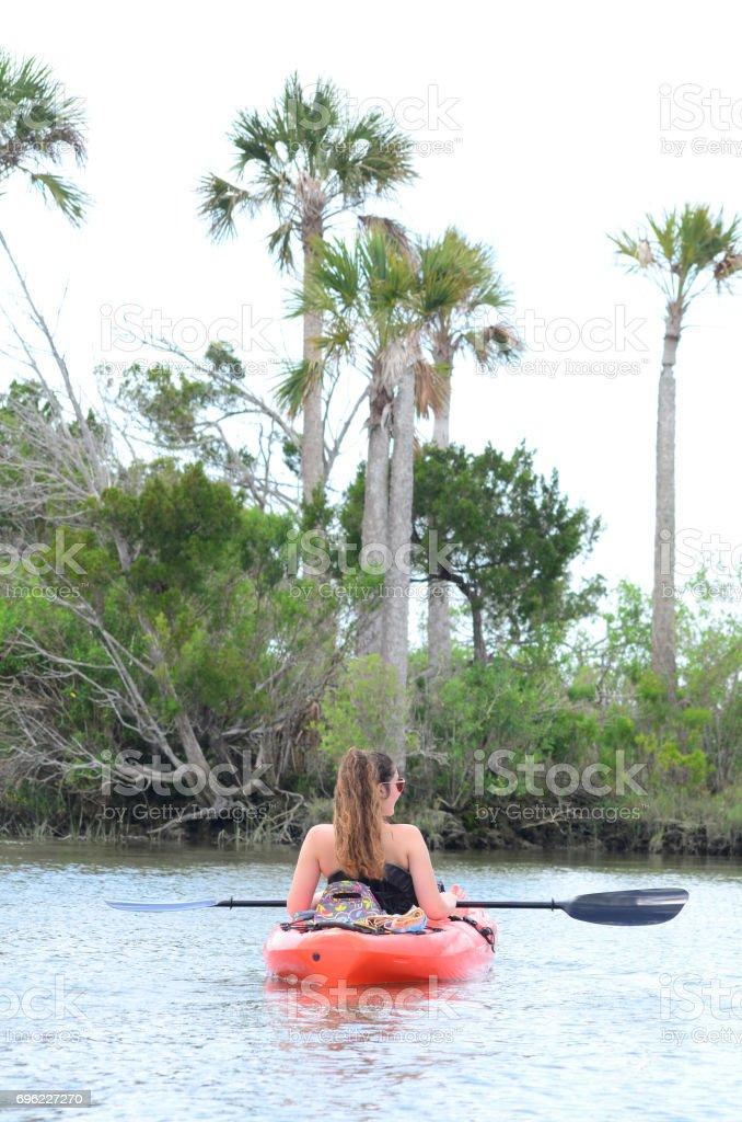 Kayaking teenage girl exploring plam covered island stock photo