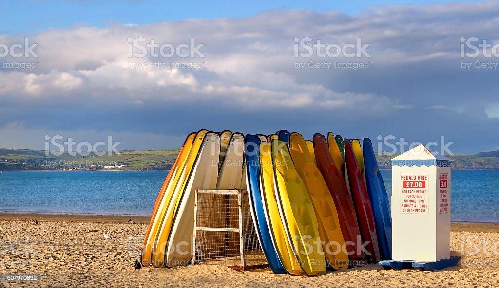 Kayaks lie unused as the sun sets over Weymouth beach stock photo