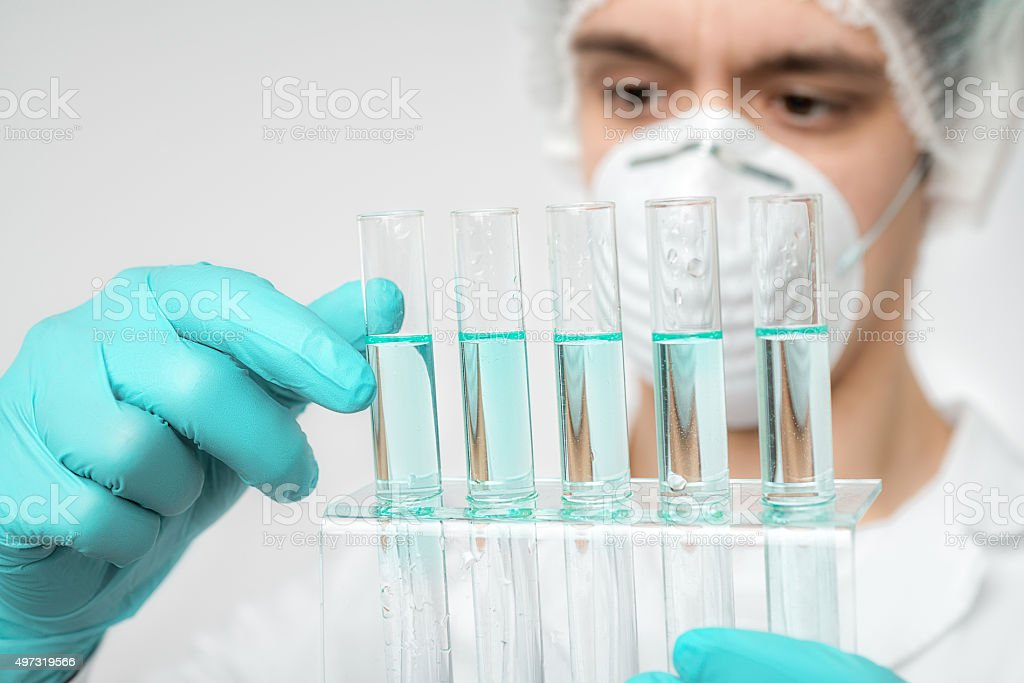 Keen scientist in protective wear performs protein assay stock photo