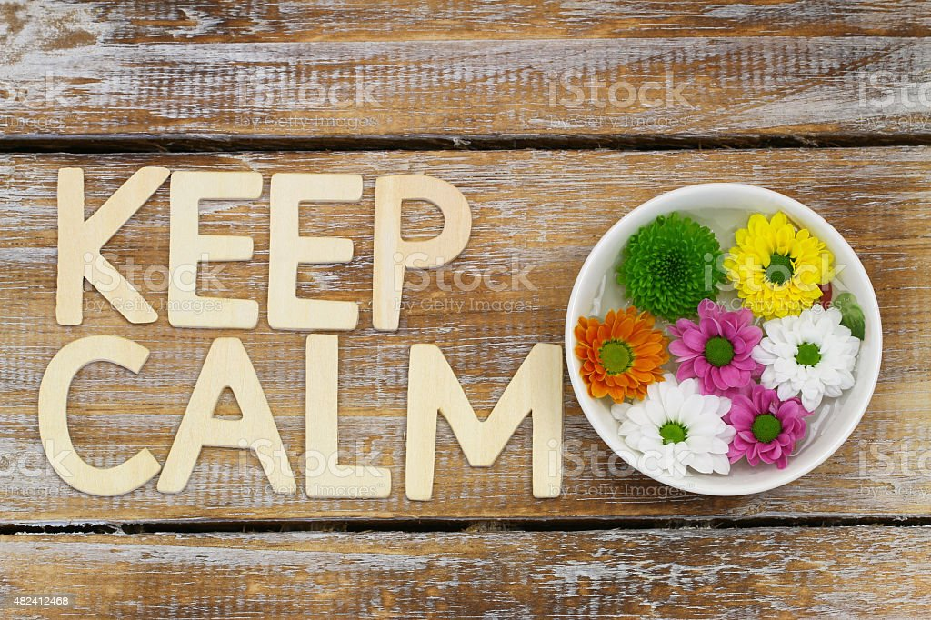 Keep calm written with wooden letters and Santini flowers stock photo