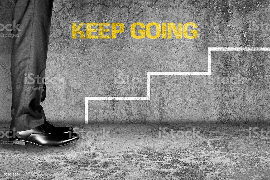 Keep Going text on wall with steps stock photo