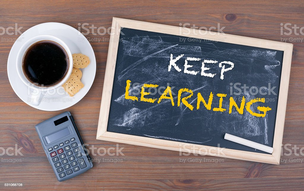 Keep Learning. Chalk board on a wooden table stock photo