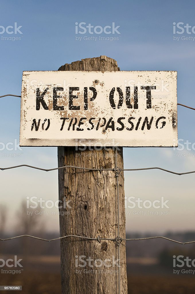 Keep Out No Trespassing Sign on Post with Blue Sky stock photo