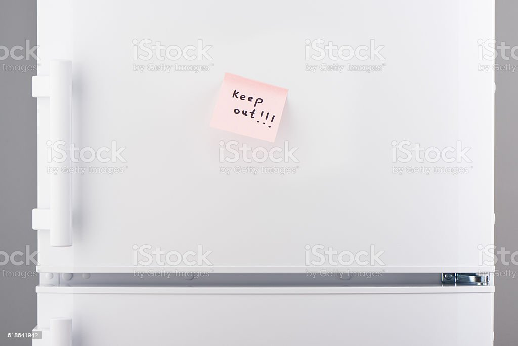 Keep out note on light pink paper on white refrigerator stock photo
