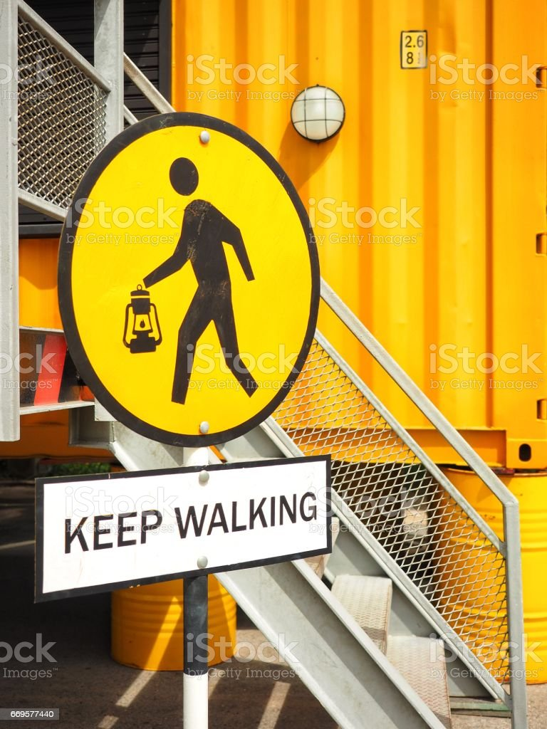 Keep walking sign in warehouse, yellow container background stock photo