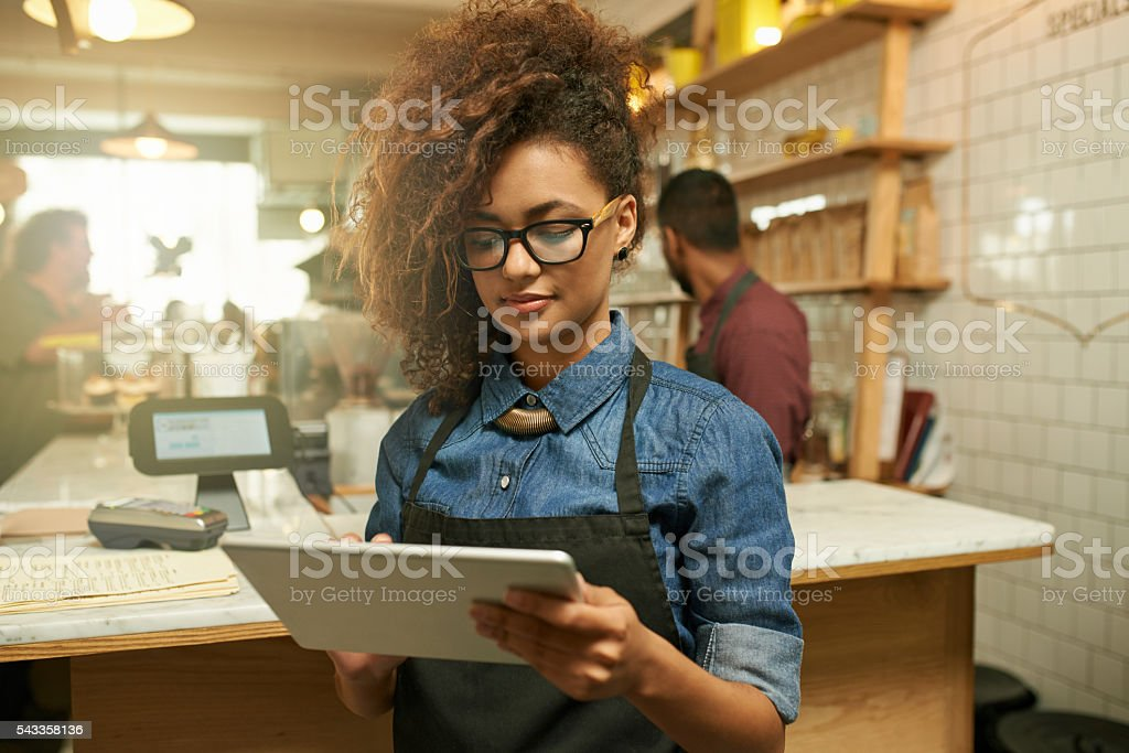 Keeping tabs on business during her shift stock photo