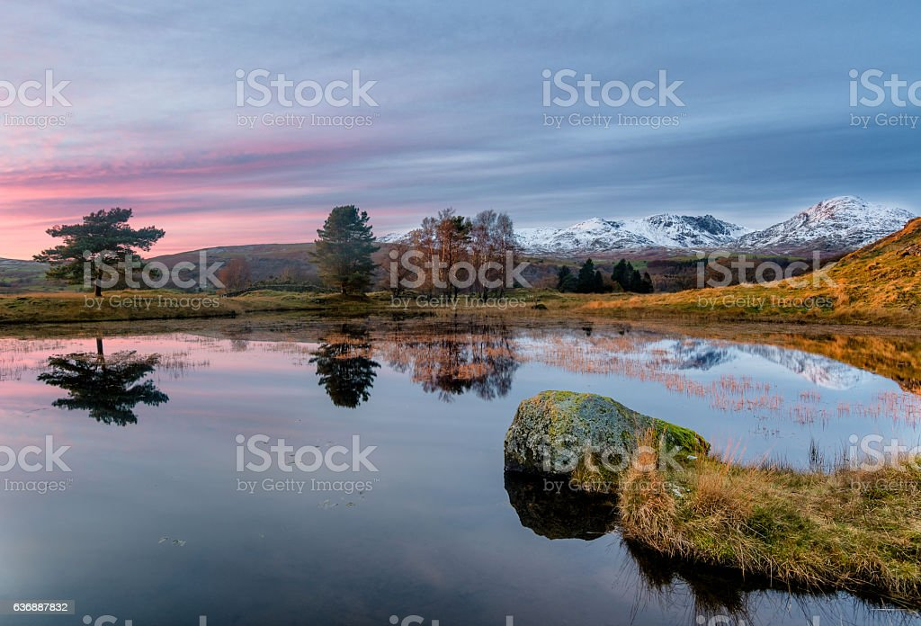 Kelly Hall Tarn Serene Sunset With Snowcapped Mountains. stock photo