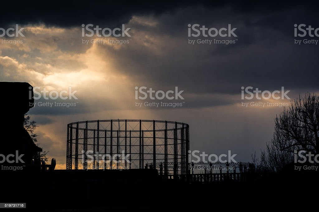 Kensal Green gasometer silhouetted in front of angry sky stock photo