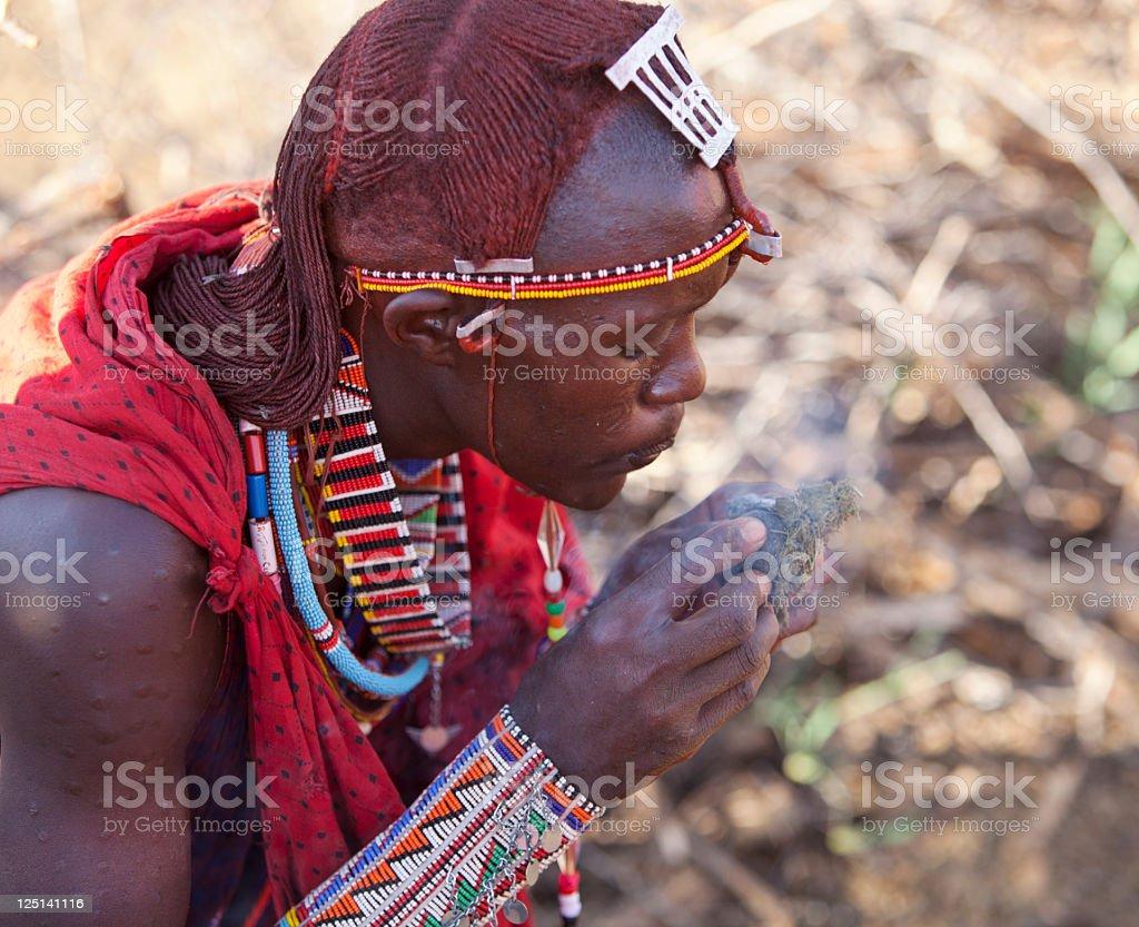Kenya Masai warrior in traditional dress making fire stock photo