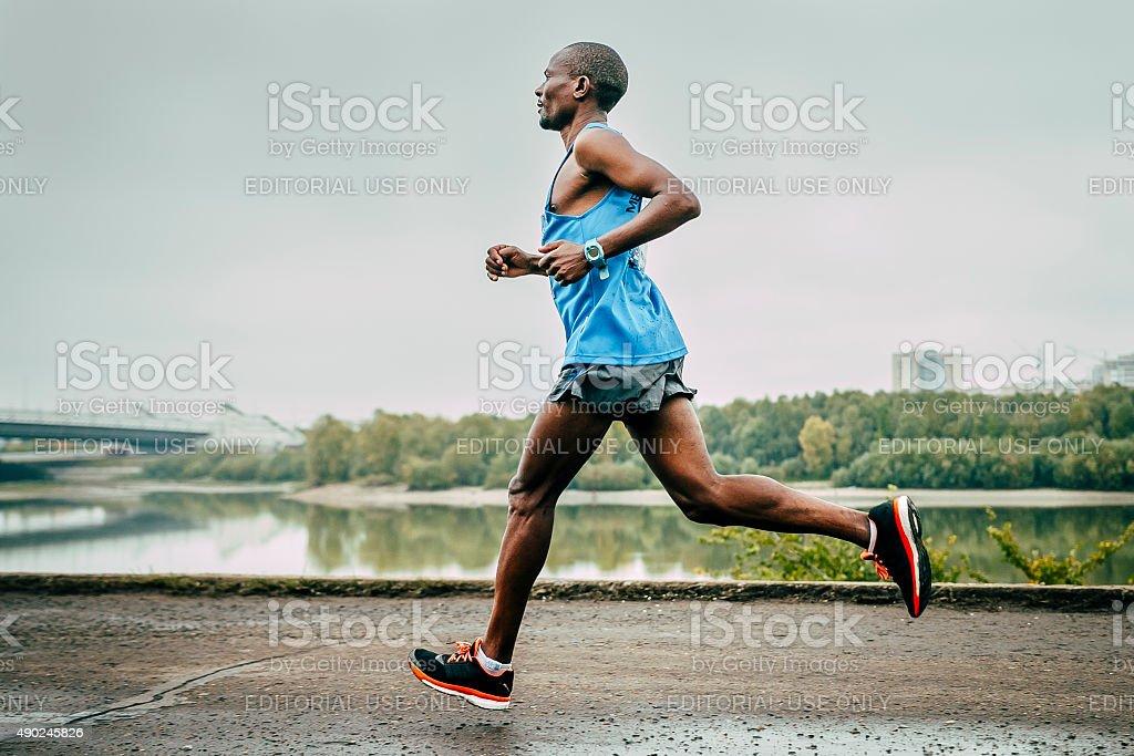 Kenyan John Kyui runs along the river stock photo