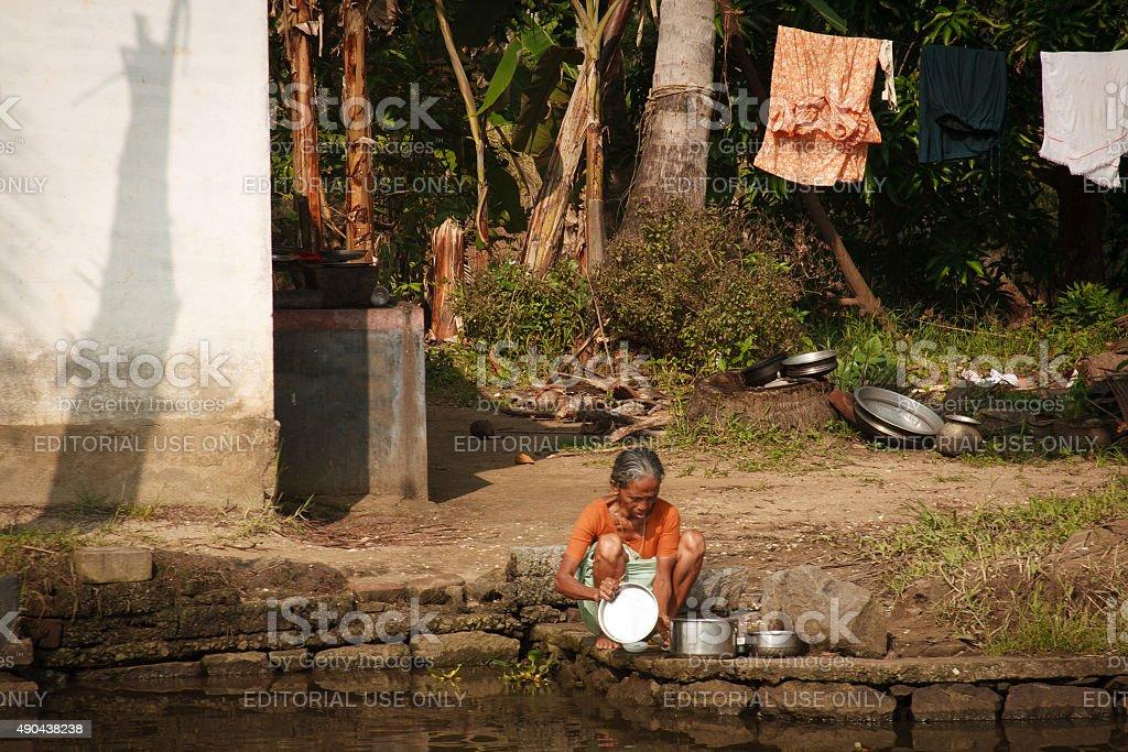 Kerala Backwaters, India: Senior Woman Washing at Lagoon's Edge stock photo