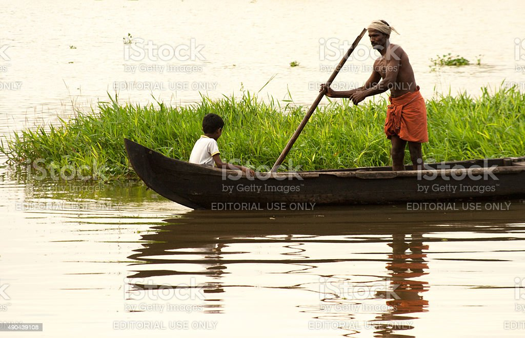 Kerala, India: Fisherman, Child, and Canoe in Kerala Backwaters stock photo