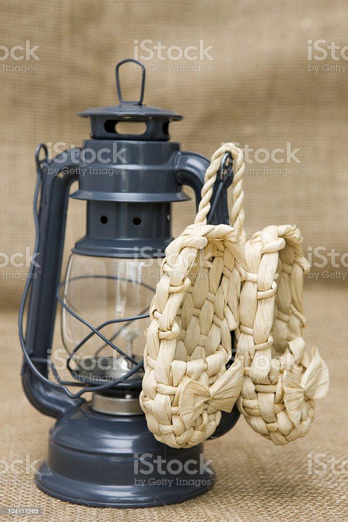 Kerosene lamp and sandals 'lapty'  on the background sacking royalty-free stock photo