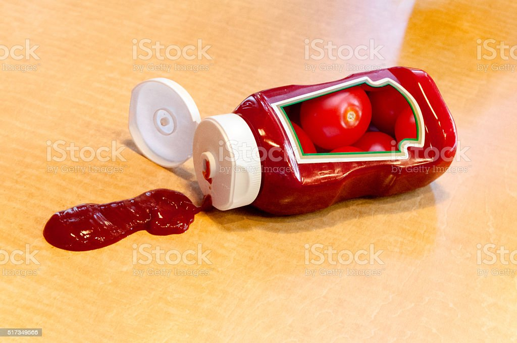 Ketchup bottle with messy spill and tomato label stock photo