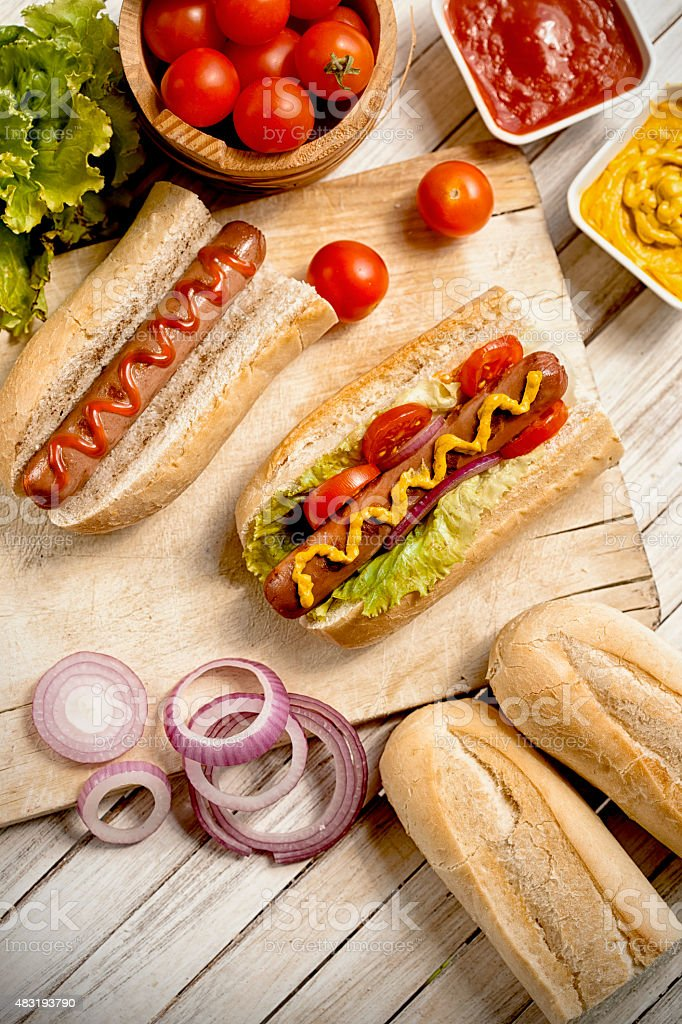 Ketchup, mustard and hotdogs on a wooden table stock photo