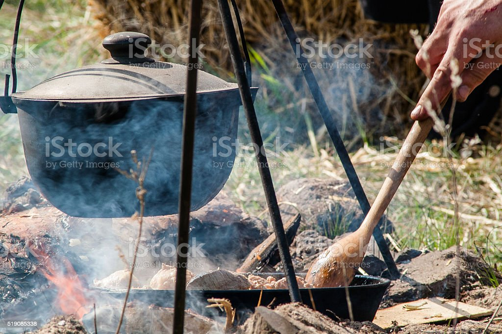 kettle on a tripod over a fire stock photo