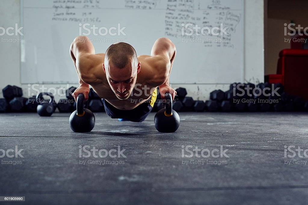 Kettlebell push-up exercise - young man doing functional workout stock photo