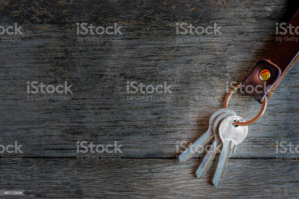 Key chain and pencil on wooden background. stock photo