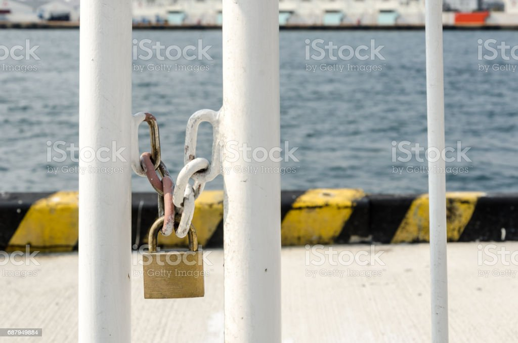Key locked on chain front of the sea, meaning security, no entry, no freedom stock photo