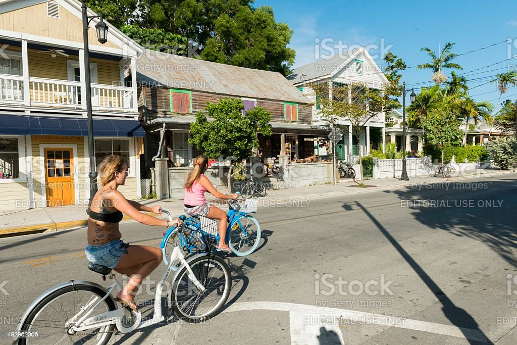 Key West Women Bike Riders on Historic Street with Architecture stock photo
