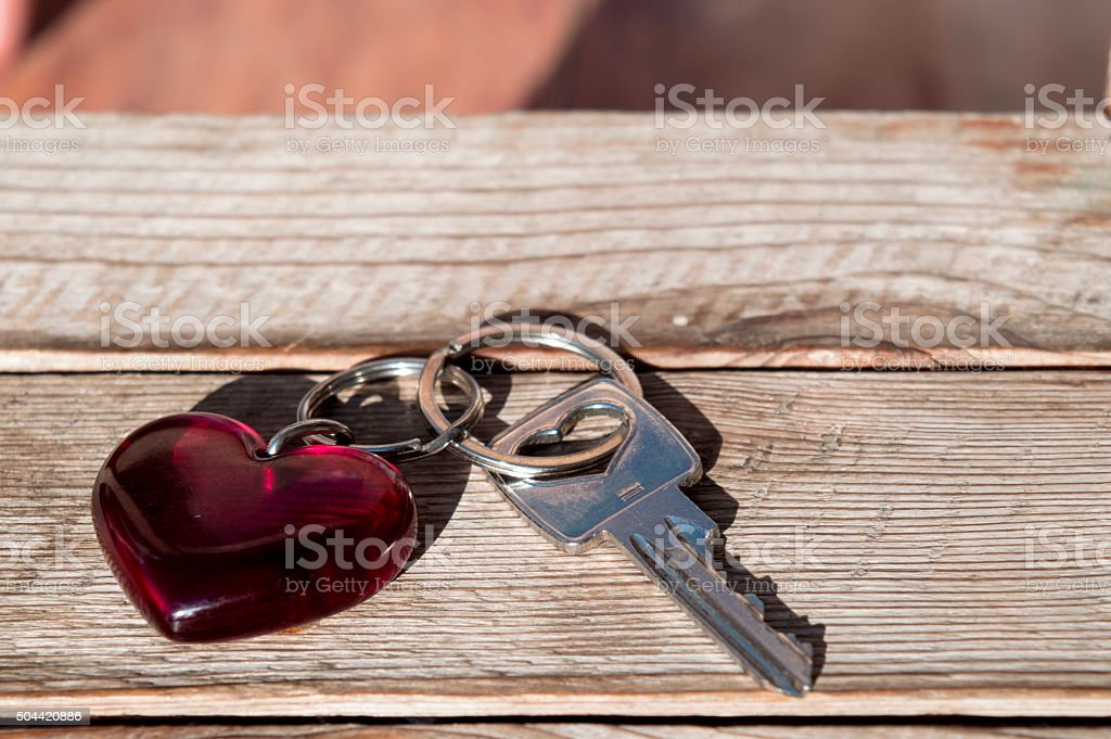 key with a heart trinket on wooden background stock photo