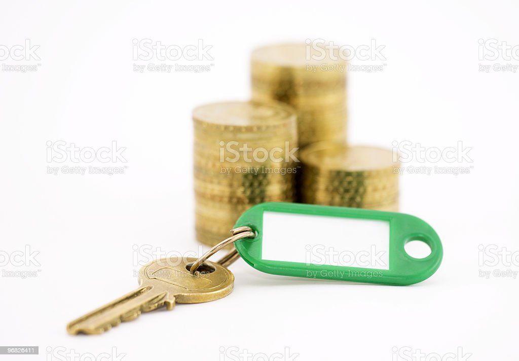 Key with coins isolated on white royalty-free stock photo