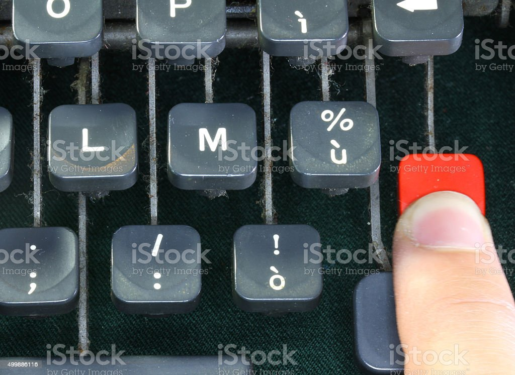 keyboard of the old typewriter with a human finger stock photo