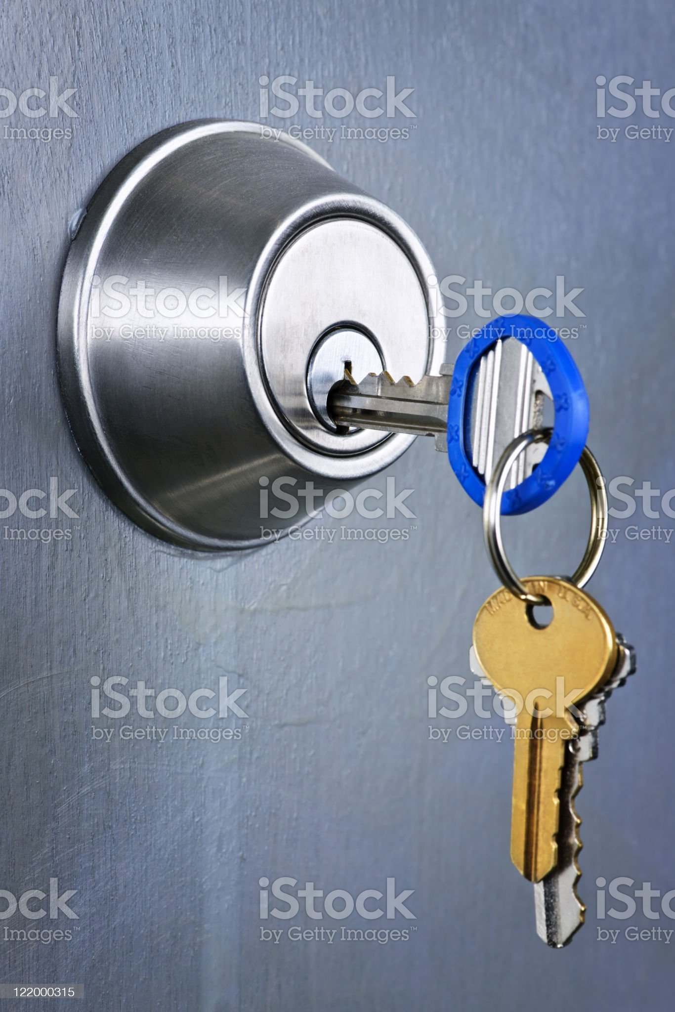 A keychain with three keys and a key in a lock royalty-free stock photo