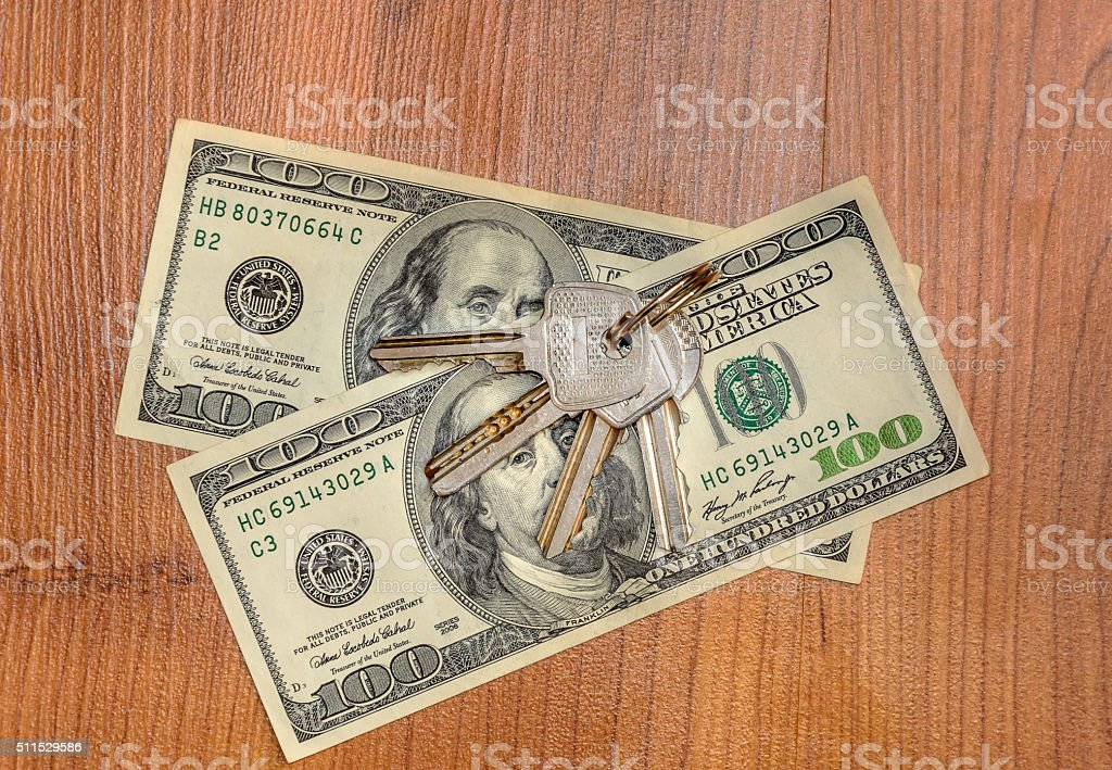 keys and dollars on wooden background stock photo