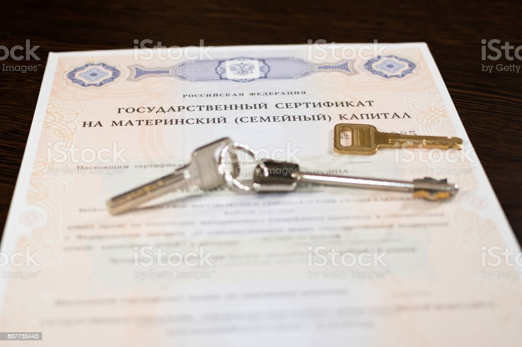 Keys from apartments are on the state certificate on the parent capital stock photo