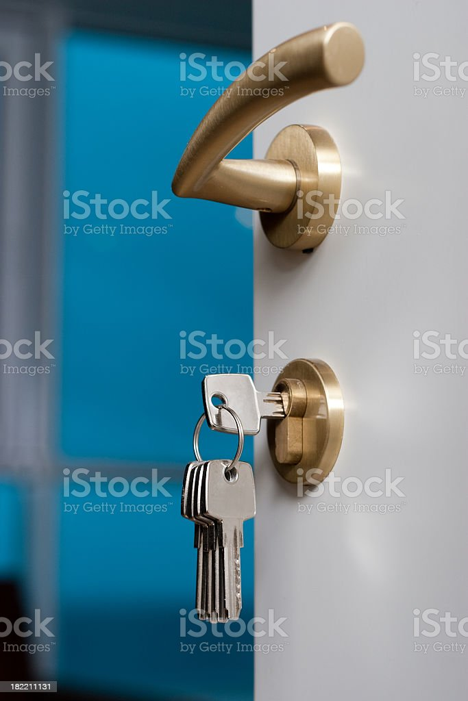 Keys hanging from open door handle stock photo