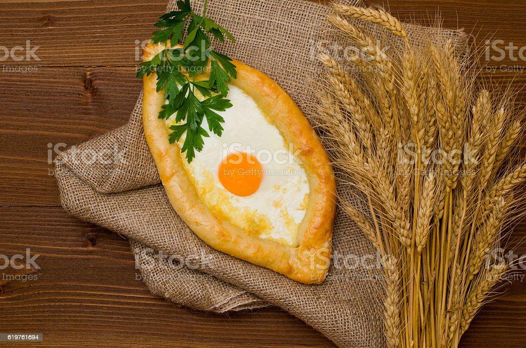 Khachapuri with egg and wheat ears on sacking stock photo