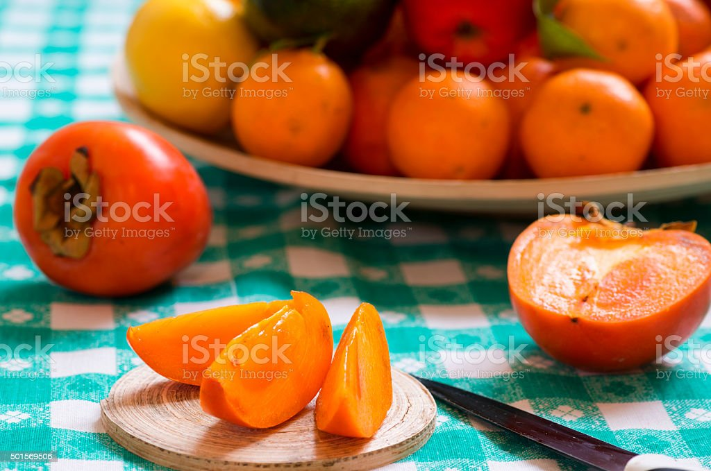 khaki fruit slices on a table stock photo