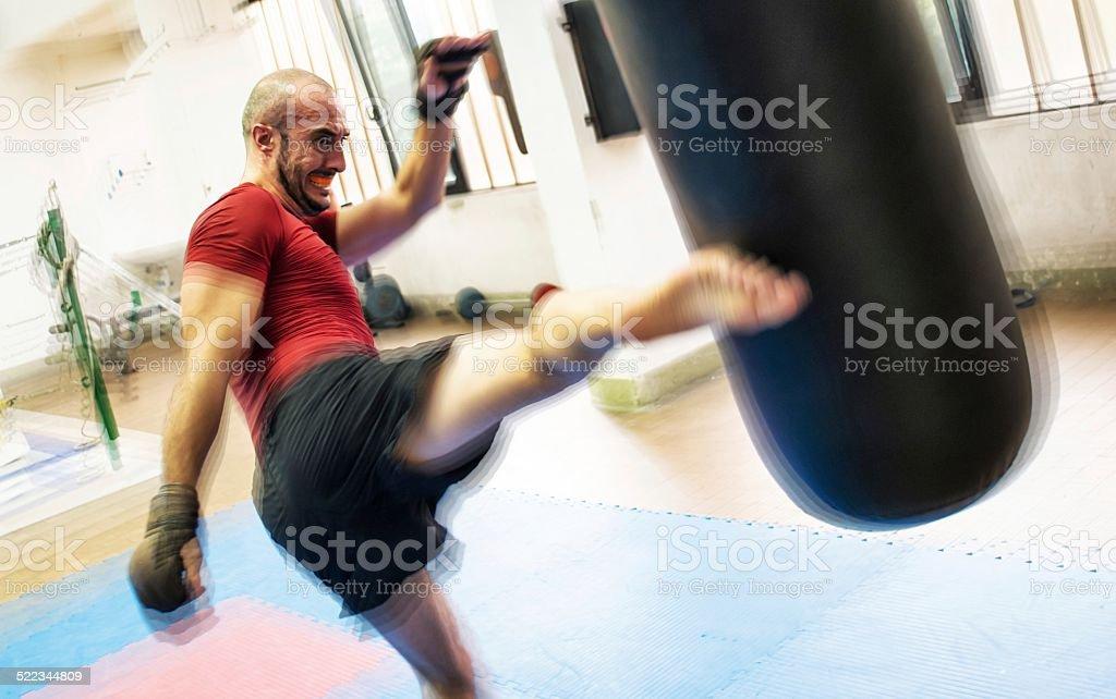 Kickboxer Striking a Punching Bag stock photo