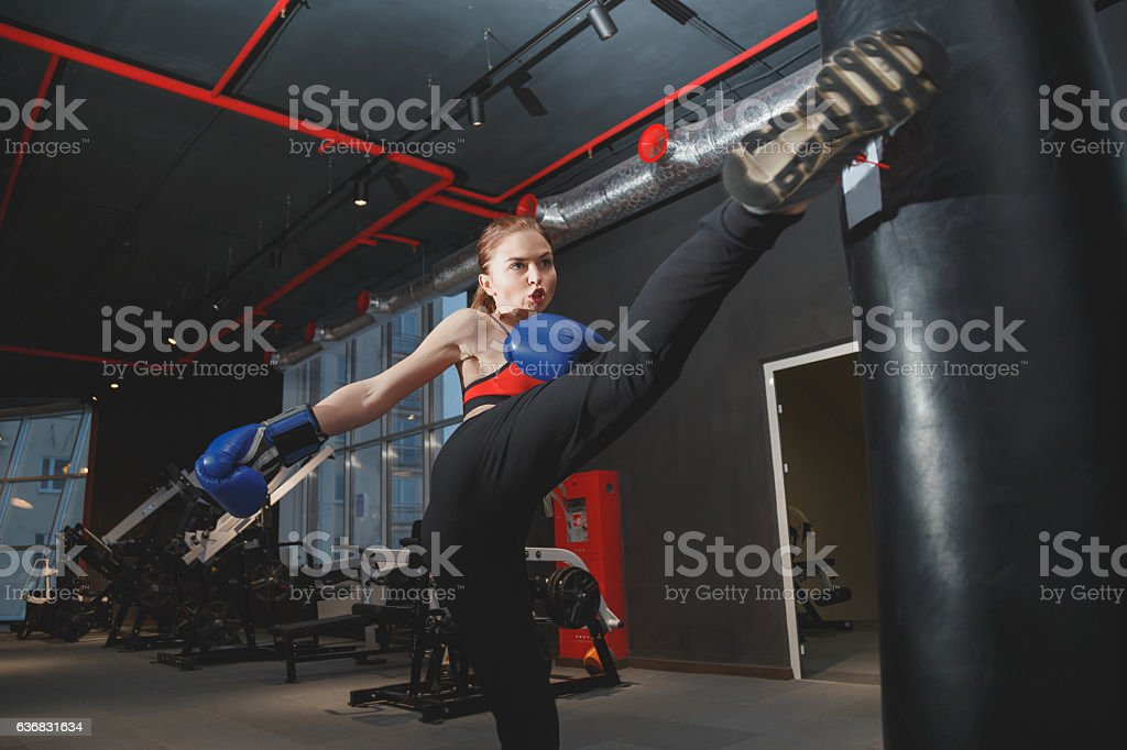 Kickboxing woman punching kicking bag at the gym stock photo