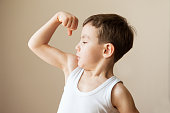 kid boy child showing muscles  fist strength training