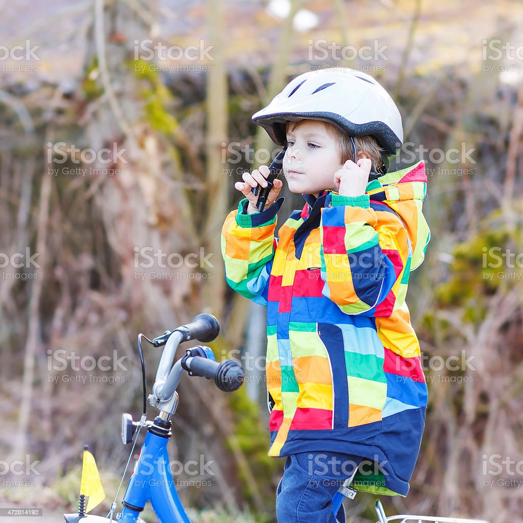 kid boy in safety helmet and colorful raincoat riding bike stock photo