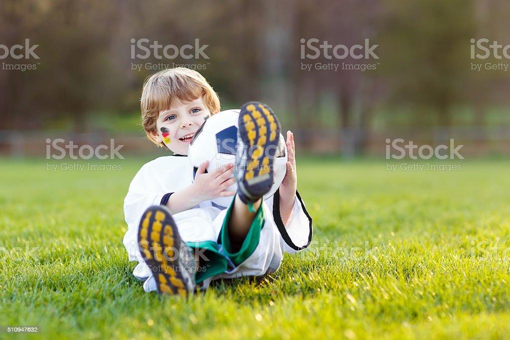 Kid boy playing soccer with football stock photo