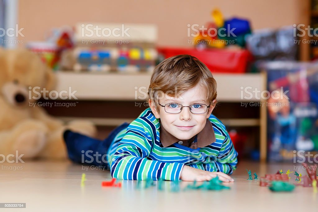 Kid boy playing with toy soldiers indoors at nursery stock photo